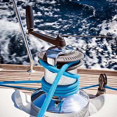 Winch with rope and crank on sailing boat.
